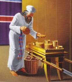 A priest changes out the bread at the Table of Showbread in the Tabernacle of Moses.