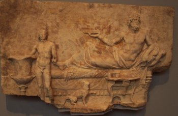 An anciennt Roman relief. A Roman god iis being served by a human subject.
